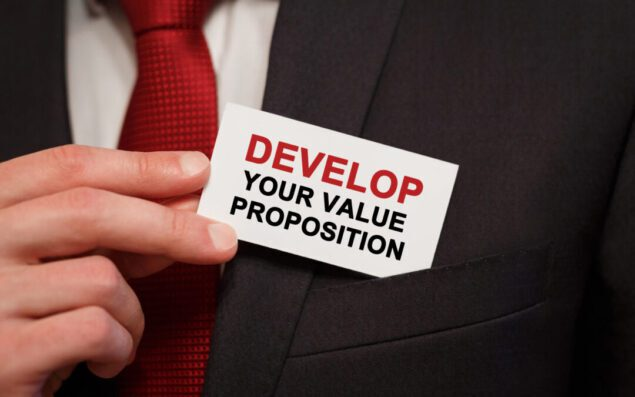 Businessman putting a card with text Develop Your Value Proposition in the pocket